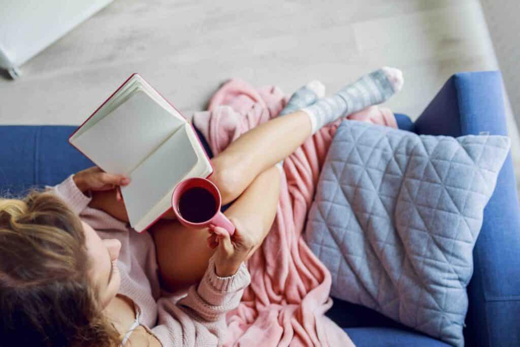 mujer leyendo libro con café