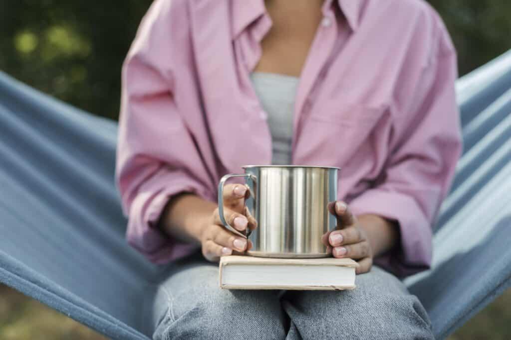 Mujer con libro autobiográfico y taza metálica