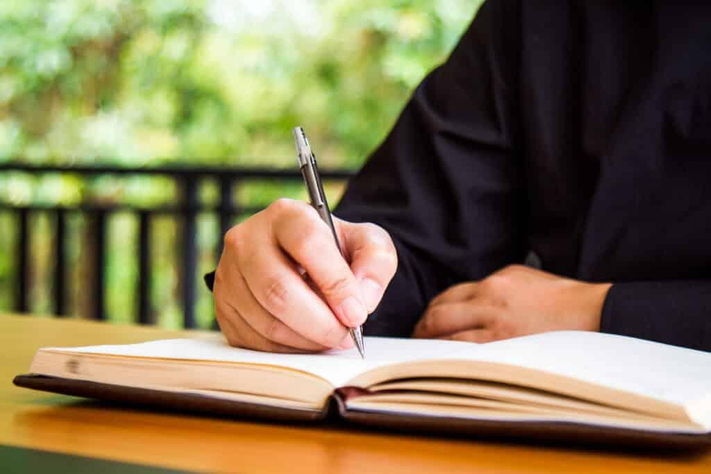 Mujer escribiendo a mano en un libro